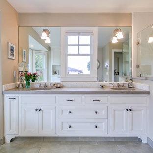 Modelo de cuarto de baño principal, costero, de tamaño medio, con armarios estilo shaker, puertas de armario blancas, bañera exenta, ducha esquinera, baldosas y/o azulejos grises, baldosas y/o azulejos de cerámica, suelo de baldosas de cerámica y encimera de cemento