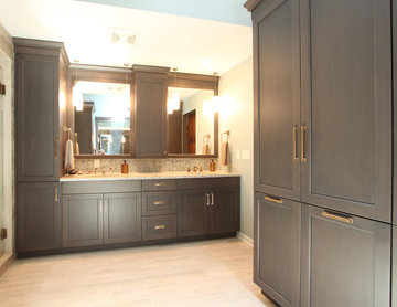 Double vanity with grey stained cabinets and tall linen storage with Brass Hardw