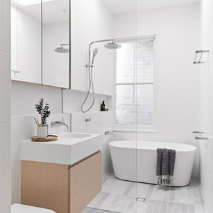 Photo of a mid-sized modern kids bathroom in Sydney with light wood cabinets, a freestanding tub, white tile, ceramic tile, white walls, porcelain floors, solid surface benchtops, grey floor, an open shower, white benchtops, a niche, a single vanity, a floating vanity, flat-panel cabinets, a curbless shower, a one-piece toilet and an integrated sink.