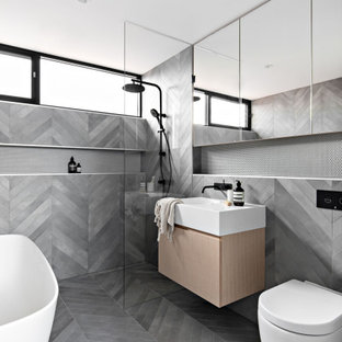 Design ideas for a mid-sized modern master bathroom in Sydney with light wood cabinets, a freestanding tub, gray tile, ceramic tile, grey walls, porcelain floors, solid surface benchtops, grey floor, an open shower, white benchtops, a niche, a single vanity, a floating vanity, flat-panel cabinets, a curbless shower, a one-piece toilet and an integrated sink.