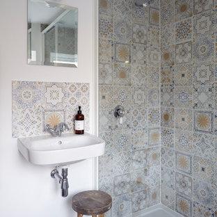 Пример оригинального дизайна: ванная комната среднего размера с открытым душем, инсталляцией, разноцветной плиткой, керамической плиткой, белыми стенами, деревянным полом, подвесной раковиной, серым полом и душем с раздвижными дверями