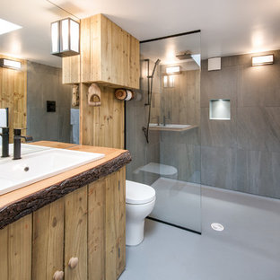 Example of a small eclectic 3/4 linoleum floor doorless shower design in Other with medium tone wood cabinets, a one-piece toilet, gray walls, a drop-in sink and wood countertops