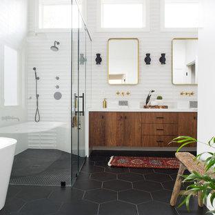 Идея дизайна: главная ванная комната среднего размера в стиле ретро с плоскими фасадами, темными деревянными фасадами, отдельно стоящей ванной, душем без бортиков, белой плиткой, керамической плиткой, белыми стенами, полом из керамогранита, настольной раковиной, столешницей из искусственного кварца, черным полом и душем с распашными дверями