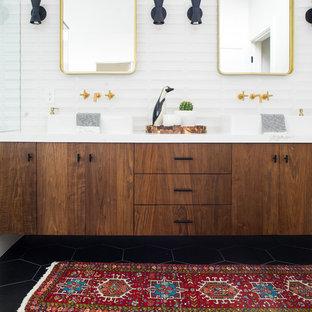 Inredning av ett 60 tals mellanstort en-suite badrum, med släta luckor, skåp i mörkt trä, ett fristående badkar, en kantlös dusch, vit kakel, keramikplattor, vita väggar, klinkergolv i porslin, ett fristående handfat, bänkskiva i kvarts, svart golv och dusch med gångjärnsdörr