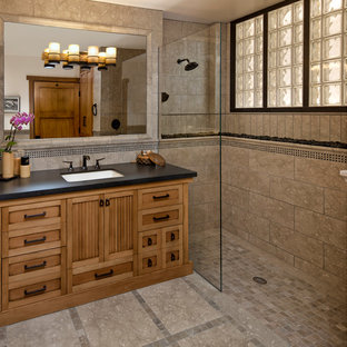 This is an example of a mid-sized asian bathroom in Santa Barbara with an undermount sink, medium wood cabinets, a curbless shower, beige tile, stone tile, limestone floors and recessed-panel cabinets.