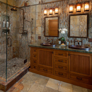 Design ideas for a mid-sized asian master bathroom in Santa Barbara with a drop-in sink, furniture-like cabinets, medium wood cabinets, granite benchtops, a corner shower, stone tile, multi-coloured walls, slate floors, brown tile and gray tile.
