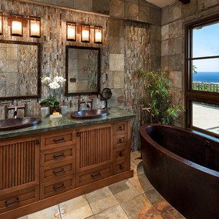 Modelo de cuarto de baño principal, de estilo zen, de tamaño medio, con lavabo encastrado, armarios tipo mueble, puertas de armario de madera oscura, encimera de granito, bañera exenta, sanitario de dos piezas, baldosas y/o azulejos de piedra, paredes multicolor, suelo de pizarra, baldosas y/o azulejos marrones y baldosas y/o azulejos grises