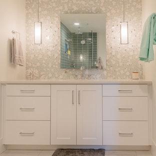 Diseño de cuarto de baño con ducha, actual, grande, con armarios con paneles lisos, puertas de armario grises, ducha esquinera, sanitario de una pieza, baldosas y/o azulejos grises, baldosas y/o azulejos de cerámica, paredes grises, suelo de baldosas de cerámica, lavabo bajoencimera, encimera de cuarcita, suelo gris y encimeras blancas