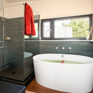 Idee per una stanza da bagno padronale nordica di medie dimensioni con vasca freestanding, doccia ad angolo, piastrelle grigie, piastrelle in ardesia, pareti bianche, pavimento in legno massello medio, top in saponaria, pavimento marrone e porta doccia a battente