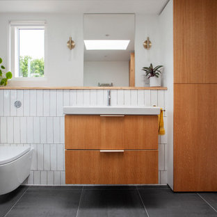 Small midcentury shower room bathroom in London with flat-panel cabinets, light wood cabinets, a built-in shower, a wall mounted toilet, white tiles, ceramic tiles, white walls, ceramic flooring, a console sink, wooden worktops, grey floors, a hinged door, brown worktops, a single sink and a floating vanity unit.