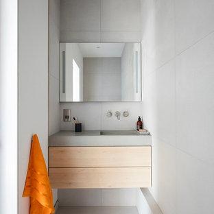 Esempio di una piccola stanza da bagno minimalista con ante in legno chiaro, zona vasca/doccia separata, WC sospeso, piastrelle in gres porcellanato, pareti grigie, pavimento in gres porcellanato, top in cemento, pavimento grigio e doccia aperta