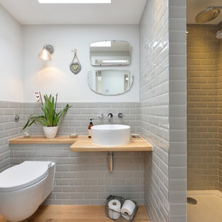 Design ideas for a classic bathroom in Other with a walk-in shower, a wall mounted toilet, grey tiles, metro tiles, white walls, medium hardwood flooring, a vessel sink, wooden worktops, an open shower and beige worktops.