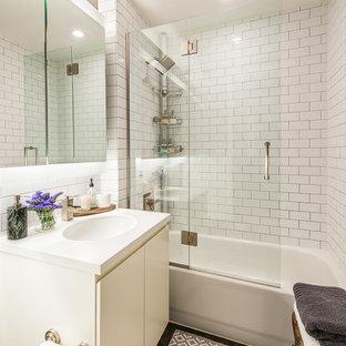 Diseño de cuarto de baño principal, ecléctico, pequeño, con lavabo bajoencimera, armarios con paneles lisos, puertas de armario blancas, encimera de cuarzo compacto, bañera exenta, combinación de ducha y bañera, sanitario de dos piezas, baldosas y/o azulejos blancos, baldosas y/o azulejos de cemento, paredes grises y suelo de pizarra