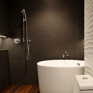Ejemplo de cuarto de baño principal, minimalista, grande, con bañera japonesa, baldosas y/o azulejos de cemento, suelo de madera oscura, armarios con paneles lisos, puertas de armario de madera en tonos medios, ducha abierta, sanitario de una pieza, paredes blancas, lavabo integrado y encimera de acrílico