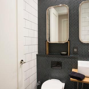 Foto di una piccola stanza da bagno classica con vasca da incasso, vasca/doccia, WC sospeso, piastrelle nere, piastrelle di vetro, pareti nere, pavimento con piastrelle a mosaico e lavabo a bacinella