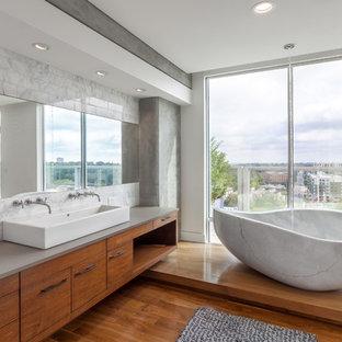 Diseño de cuarto de baño actual con armarios con paneles lisos, puertas de armario de madera oscura, bañera exenta, paredes blancas, suelo de madera en tonos medios y lavabo de seno grande