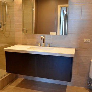 シカゴのコンテンポラリースタイルのおしゃれなマスターバスルーム (フラットパネル扉のキャビネット、黒いキャビネット、珪岩の洗面台、グレーのタイル) の写真