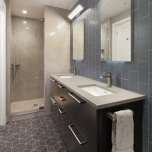 ワシントンD.C.の中サイズのコンテンポラリースタイルのおしゃれなバスルーム (浴槽なし) (フラットパネル扉のキャビネット、黒いキャビネット、一体型トイレ、グレーのタイル、サブウェイタイル、クッションフロア、アンダーカウンター洗面器、アルコーブ型シャワー、グレーの壁、人工大理石カウンター) の写真