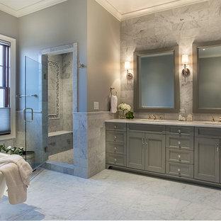 Bild på ett stort vintage en-suite badrum, med luckor med infälld panel, grå skåp, ett fristående badkar, en dusch i en alkov, grå kakel, vit kakel, stenkakel, grå väggar, marmorgolv, ett undermonterad handfat och bänkskiva i akrylsten