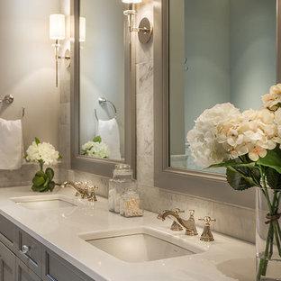 Ispirazione per una grande stanza da bagno padronale chic con ante grigie, pareti grigie, lavabo sottopiano, ante con riquadro incassato, vasca freestanding, piastrelle grigie, piastrelle bianche, pavimento in marmo, top in superficie solida e piastrelle di marmo
