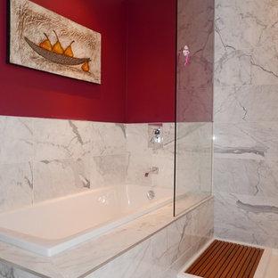トロントの大きいトランジショナルスタイルのおしゃれなマスターバスルーム (フラットパネル扉のキャビネット、白いキャビネット、ドロップイン型浴槽、コーナー設置型シャワー、一体型トイレ、グレーのタイル、大理石タイル、赤い壁、大理石の床、一体型シンク、人工大理石カウンター、グレーの床、オープンシャワー) の写真