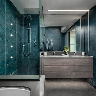 Modelo de cuarto de baño principal, actual, de tamaño medio, con armarios con paneles lisos, puertas de armario grises, bañera encastrada sin remate, ducha esquinera, baldosas y/o azulejos azules, baldosas y/o azulejos de porcelana, paredes grises, suelo de baldosas de porcelana, lavabo bajoencimera, encimera de cuarzo compacto, suelo gris, ducha con puerta con bisagras y encimeras grises
