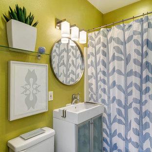 Diseño de cuarto de baño actual con lavabo sobreencimera, armarios tipo vitrina, bañera empotrada, combinación de ducha y bañera y sanitario de dos piezas