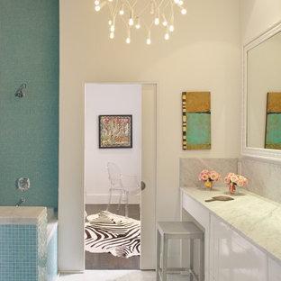 Foto di una stanza da bagno minimalista con vasca ad alcova, vasca/doccia, piastrelle blu e piastrelle a mosaico