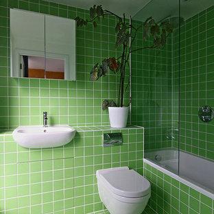 Ejemplo de cuarto de baño principal, minimalista, de tamaño medio, con puertas de armario verdes, bañera encastrada, combinación de ducha y bañera, sanitario de pared, baldosas y/o azulejos verdes, baldosas y/o azulejos de cerámica, paredes verdes, suelo de baldosas de cerámica, lavabo encastrado, encimera de azulejos, suelo verde y encimeras verdes