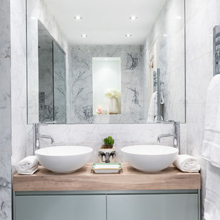 This is an example of a medium sized contemporary ensuite bathroom in London with flat-panel cabinets, blue cabinets, an alcove shower, grey tiles, marble flooring, a vessel sink, wooden worktops, black floors and brown worktops.