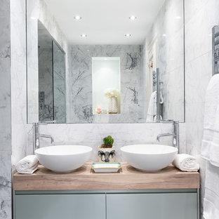 Bild på ett mellanstort funkis brun brunt en-suite badrum, med släta luckor, blå skåp, en dusch i en alkov, grå kakel, marmorgolv, ett fristående handfat, träbänkskiva och svart golv
