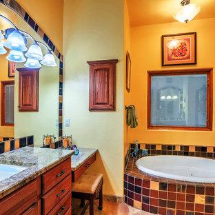 Idee per una stanza da bagno padronale american style di medie dimensioni con ante in legno scuro, top in granito, top marrone, ante lisce, vasca ad angolo, piastrelle multicolore, piastrelle in ceramica, pareti gialle, pavimento in ardesia, lavabo sottopiano e pavimento multicolore