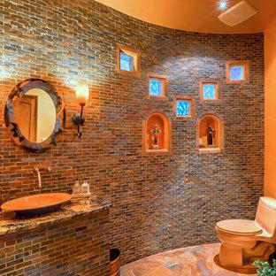 Modelo de cuarto de baño de estilo americano, de tamaño medio, con armarios con paneles empotrados, puertas de armario de madera oscura, baldosas y/o azulejos rojos, encimera de granito y encimeras marrones