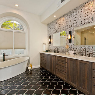 Cette photo montre une grand douche en alcôve principale chic avec un placard avec porte à panneau encastré, une baignoire indépendante, un WC suspendu, un carrelage gris, des carreaux en terre cuite, un mur blanc, un sol en carreau de terre cuite, un lavabo encastré, un plan de toilette en quartz modifié et des portes de placard en bois sombre.