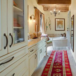 Bild på ett stort amerikanskt en-suite badrum, med luckor med infälld panel, beige skåp, ett platsbyggt badkar, beige kakel, blå kakel, brun kakel, keramikplattor, gula väggar, klinkergolv i porslin och ett undermonterad handfat