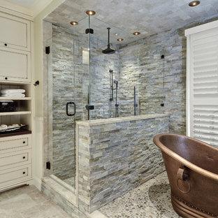 Foto på ett stort vintage vit en-suite badrum, med ett fristående badkar, stenkakel, klinkergolv i småsten, luckor med profilerade fronter, beige skåp, en hörndusch, grå kakel, beige väggar, bänkskiva i kvarts och grått golv