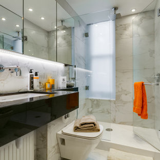 Medium sized contemporary shower room bathroom in London with open cabinets, black cabinets, an alcove shower, a wall mounted toilet, grey tiles, porcelain tiles, porcelain flooring, a submerged sink, grey floors, a hinged door and black worktops.