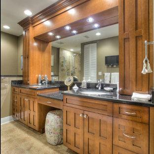 Diseño de cuarto de baño principal, tradicional, grande, con armarios con paneles empotrados, puertas de armario de madera oscura, ducha empotrada, sanitario de una pieza, paredes beige, suelo de linóleo, lavabo bajoencimera, encimera de granito, suelo beige y ducha con puerta con bisagras