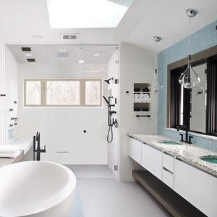 Свежая идея для дизайна: большая главная ванная комната в современном стиле с белыми фасадами, отдельно стоящей ванной, душем без бортиков, белой плиткой, керамической плиткой, полом из керамогранита, врезной раковиной, столешницей из переработанного стекла, серым полом, душем с распашными дверями, плоскими фасадами, белыми стенами и серой столешницей - отличное фото интерьера