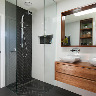 Inspiration for a contemporary bathroom in Wollongong with flat-panel cabinets, medium wood cabinets, a curbless shower, black tile, white walls and a vessel sink.