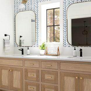 ミネアポリスのトランジショナルスタイルのおしゃれな浴室 (シェーカースタイル扉のキャビネット、淡色木目調キャビネット、青い壁、モザイクタイル、アンダーカウンター洗面器、マルチカラーの床、白い洗面カウンター、洗面台2つ、造り付け洗面台、壁紙) の写真