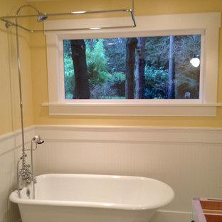 Ispirazione per una piccola stanza da bagno con doccia classica con ante a filo, ante bianche, vasca con piedi a zampa di leone, vasca/doccia e pareti gialle