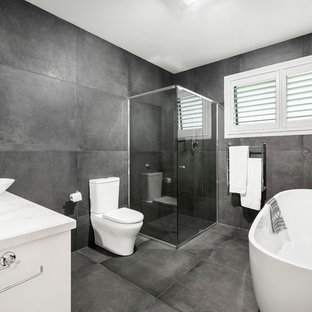 Inspiration for a contemporary master bathroom in Melbourne with a freestanding tub, a corner shower, a two-piece toilet, grey walls, a vessel sink, grey floor and a hinged shower door.