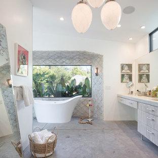 Imagen de cuarto de baño principal, retro, grande, con armarios con paneles lisos, puertas de armario de madera clara, paredes blancas, lavabo integrado, bañera exenta, suelo gris y suelo de cemento