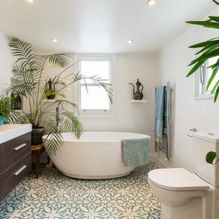 Idéer för ett modernt vit en-suite badrum, med släta luckor, skåp i mörkt trä, ett fristående badkar, en toalettstol med separat cisternkåpa, vita väggar, ett integrerad handfat och flerfärgat golv