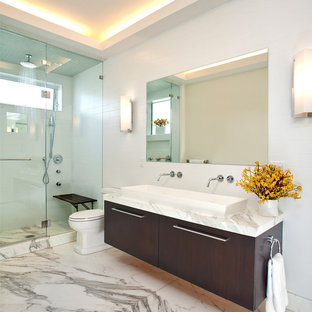 Inspiration for a modern white tile marble floor alcove shower remodel in San Francisco with a trough sink, flat-panel cabinets and dark wood cabinets