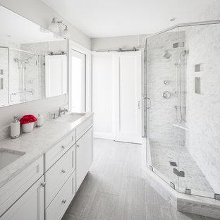 Immagine di una stanza da bagno con doccia tradizionale di medie dimensioni con ante in stile shaker, ante bianche, doccia ad angolo, WC a due pezzi, piastrelle grigie, piastrelle bianche, piastrelle di marmo, pareti grigie, pavimento in vinile, lavabo sottopiano, top in quarzite, pavimento grigio e porta doccia a battente