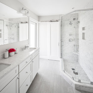 Mid-sized transitional 3/4 gray tile, white tile and marble tile vinyl floor and gray floor corner shower photo in Boston with shaker cabinets, white cabinets, a two-piece toilet, gray walls, an undermount sink, quartzite countertops and a hinged shower door