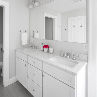 Mittelgroßes Klassisches Duschbad mit Schrankfronten im Shaker-Stil, weißen Schränken, Eckdusche, Wandtoilette mit Spülkasten, grauen Fliesen, weißen Fliesen, Marmorfliesen, grauer Wandfarbe, Vinylboden, Unterbauwaschbecken, Quarzit-Waschtisch, grauem Boden und Falttür-Duschabtrennung in Boston