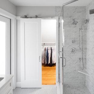 Diseño de cuarto de baño con ducha, clásico renovado, de tamaño medio, con armarios estilo shaker, puertas de armario blancas, ducha esquinera, sanitario de dos piezas, baldosas y/o azulejos grises, baldosas y/o azulejos blancos, baldosas y/o azulejos de mármol, paredes grises, suelo vinílico, lavabo bajoencimera, encimera de cuarcita, suelo gris y ducha con puerta con bisagras